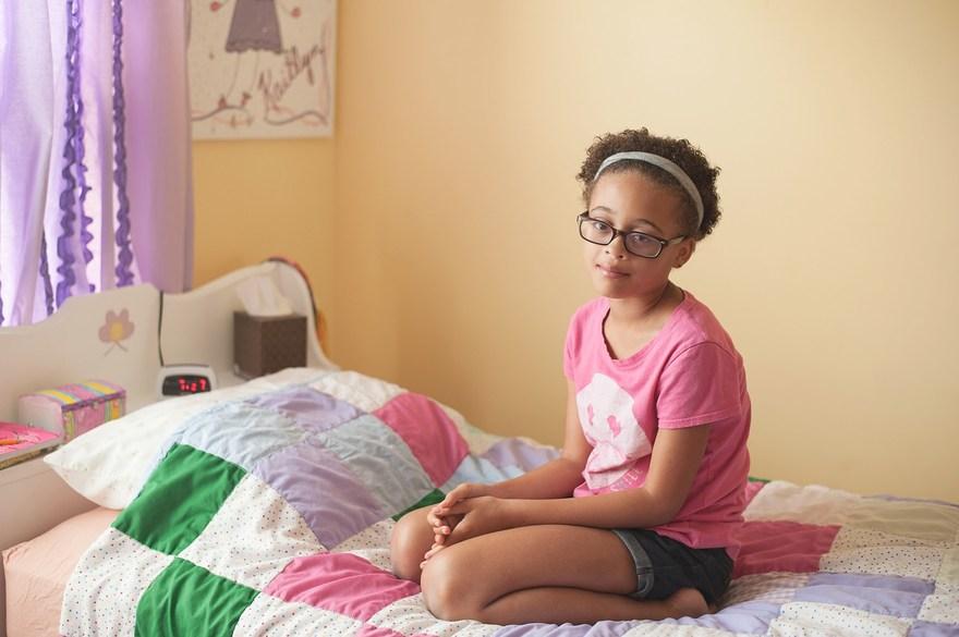 Photographers in Greensboro NC with tween girl kneeling on bed