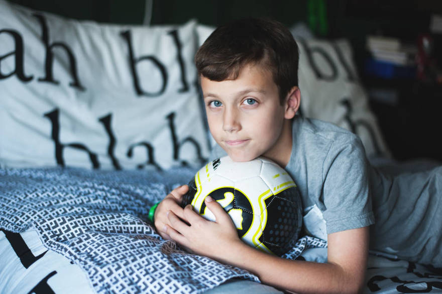 Photographers in Greensboro NC with tween boy on bed with soccer ball